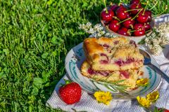 Portion of cherry cake with ripe strawberries around and few yellow blooms Stock Photo