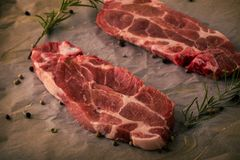 Two pieces of raw pork steaks with rosemary and pepper seeds on paper sheet. Horizontal photo of two slices of pork neck steaks. The meat portions with red color stock photos
