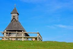 Wooden Chapel of Our Lady of the Snows. Horizontal photo of the wooden chapel with blue sky and the moon for the background stock photography