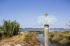 Wooden signpost for biking trails with arrows pointing direction of the road. Rural environment close to estuary water. Horizontal photo of wooden signpost for stock images