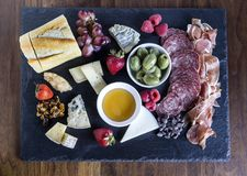 Chesse Board with Olives and Charcuterie. Horizontal photograph of a cheese board with Charcuterie and fruit stock images