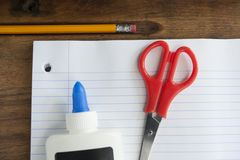 Pencil, Scissors and a Bottle of Glue on Notebook Paper royalty free stock images