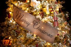 Merry Christmas Sign in a Christmas Tree Stock Photos