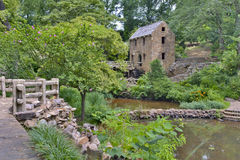 A horizontal photograph of a stone and concrete old mill, Side View Stock Images