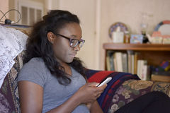 Horizontal photographs of African girl. Head and shoulders photograph of a African girl with long black hair wearing glasses and a gray T-shirt, reading text Stock Photos