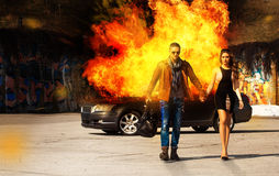 Horizontal picture of the blockbuster as a man and a woman go aw. Horizontal picture of the blockbuster as a men and a women go away from burning car outdoors Royalty Free Stock Photography