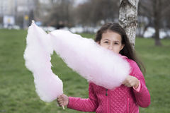 Horizontal picture of cute preteen girl eating cotton candy Stock Images