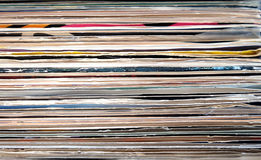 Horizontal pile of many close standing vinyl records covers as background front view closeup Royalty Free Stock Image