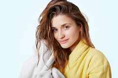 Horizontal portrait of adorable female model with healthy pure skin has wet hair, wears warm bathrobe, wipes hair with towel, take Stock Image