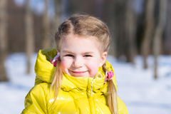 Adorable little girl in a yellow winter jacket Stock Images
