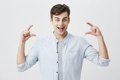 Amazed surprised european young male model joyfully smiling with with opened mouth, demonstrating size with both hands Stock Photo
