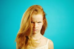 Horizontal portrait of angry red haired girl with gloomy expression demonstrates anger and dissatisfaction, has bad mood. And capricious character, shot of stock image