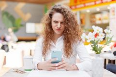 Horizontal portrait of anxious discontent female model recieves message of remainder to pay bills, frowns face in displeasure, hol. Ds modern smart phone, drinks Royalty Free Stock Photography