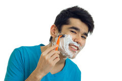 Horizontal portrait of attractive young guy who smiles and shaves his beard machine close-up Stock Image