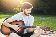 Horizontal portrait of bearded fashionable guy sitting crossed legs playing guitar while resting at green grass admiring sunshine. Stock Photos