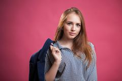 Horizontal portrait of a beautiful red haired student girl on a pink background royalty free stock image