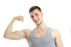 Horizontal portrait of beautiful sports guy who smiles and shows his muscle on hand Stock Images