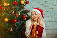 Horizontal portrait of beautiful young blonde in santa hat with Stock Photography