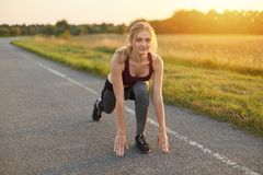 Horizontal portrait of blonde female, wearing top, trousers and sport shoes, doing exercises on road, stretching her legs, being f stock image