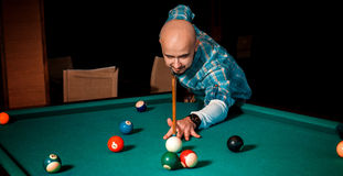 Horizontal portrait of concentrated man plays on billiard table Stock Images