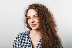 Horizontal portrait of delighted pleasant looking young female with curly hair, blue eyes and healthy skin, wears casual checkered stock images