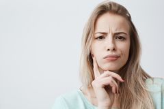 Horizontal portrait of displeased woman with blonde hair has indignant expression of face, frowns eyebrows, can t royalty free stock photography