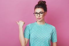 Horizontal portrait of elegance woman with hair bun and glasses, pointing on copy space with finger isolated over pink background. Beautiful female showing Royalty Free Stock Image