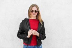 Horizontal portrait of fashionable female wearing black jacket, red sweater and trendy sunglasses having rucksack on her back isol Royalty Free Stock Photography
