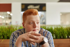 A horizontal portrait of freckled redhead boy wearing checked shirt and elegant watch sitting over green plantations holding his h Royalty Free Stock Image