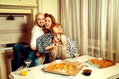 Horizontal portrait of fun three people at a party with pizza an Stock Images