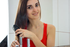 Horizontal portrait of girl smiling that combing her hair and looking at camera Royalty Free Stock Photo