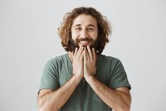 Horizontal portrait of handsome eastern man with curly hair and beard holding hands on chin while smiling cheerfully stock images
