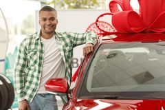 Handsome African man choosing new car at dealership royalty free stock image