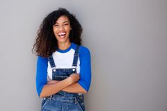 Portrait of happy young african american woman laughing against gray wall royalty free stock image