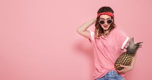 Portrait of hipster girl in glasses and pineapple on pink background stock images