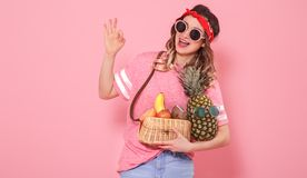 Portrait of a girl with healthy food, fruits, on a pink background royalty free stock photos