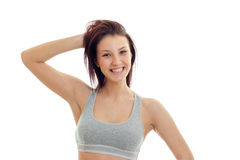 Horizontal portrait of joyous beautiful brunette that stands in a gray top looks straight and laughs Stock Images