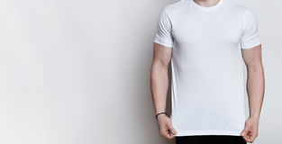 A horizontal portrait of muscular young man wearing white T-shirt posing in a studio over white background with empty space. Mock Stock Photography