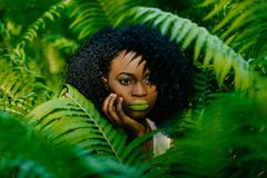 Horizontal portrait. The pretty attractive african girl with green lipstick and eyeshadows tenderly touching her face. Being surrounded by ferns royalty free stock photo