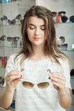 Horizontal portrait of pretty caucasian student in optician store picking perfect pair of sunglasses to match with her royalty free stock images