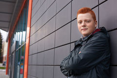 A horizontal portrait of redhead guy with freckles wearing black jacket posing over black wall of the shop. A handsome stylish guy Stock Photo