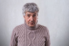 A horizontal portrait of senior handsome man standing against white wall wearing sweater looking with astonishment into camera. Pe Royalty Free Stock Photos