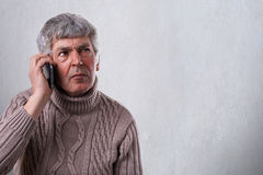 A horizontal portrait of serious, worried, upset mature man talkiing on cellphone. An old employee deciding some problems over tel. Ephone. Human face expression Stock Photography