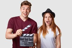 Horizontal portrait of shocked young successful female actress and her producer holds clapperboard, has cheerful expression, creat. New production of film Royalty Free Stock Image