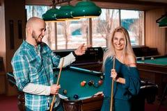 Horizontal portrait of smiling beautiful couple plays billiard. American pool billiard. Billiard sport concept. Pool billiard game royalty free stock images