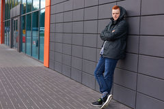 A horizontal portrait of young fashionable guy with trendy red hair dressed in black jacket, jeans and running shoes having hood o Royalty Free Stock Image