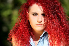 Horizontal portrait of a young girl with red curly hair. And nose piercing. The girl has a serious attitude Stock Photo