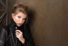 Horizontal portrait of young sexy woman in rock. Black leather jacket, an earring and a ring. Collected hair, professional makeup. Rusty metal wall in the Royalty Free Stock Image