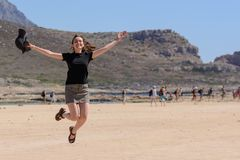 Horizontal portrait of a young woman on vacation, happy jumping up on the beach. copy space stock photos