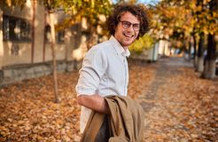 Horizontal potrait of young businessman with glasses posing outdoors going to the lunch. Male student in autumn street. Smart guy royalty free stock photos
